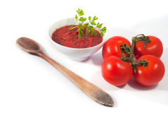 Tomato sauce on white bowl with some raw tomatoes isolated on white. Background royalty free stock photography