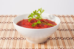 Tomato sauce on white bowl with wooden place mat Stock Images