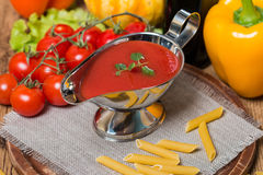 Tomato sauce in a white sauce boat with fresh ingredients Stock Images