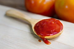 Tomato sauce on wooden chopping board. Closeup of sauce Stock Photography