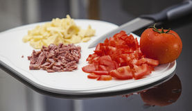 Tomato, sausage and cheese sliced. On white cutting Board Royalty Free Stock Photography