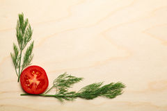 Tomato slice and dill twigs on chopping board Royalty Free Stock Photography