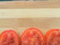 Tomato slice line on wooden background Stock Photography