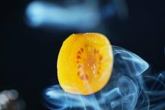 Tomato slice and smoke photographed Royalty Free Stock Photography
