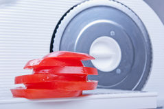 Tomato sliced with a slicer. Slices of tomato lying at the food slicer Stock Images