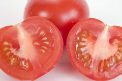 Tomato Slices. Whole tomato and two tomato slices showing seeds royalty free stock image