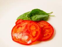 Tomato slices with basilic leaf Stock Images