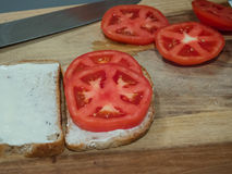 Tomato Slices on Bread Sandwich. Making a tomato sandwich with slices of bread with mayonnaise on a cutting board with knife stock photos