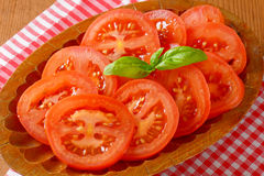 Tomato slices. Detail of tomato slices and fresh basil on oval wooden plate and checkered dishtowel Stock Image