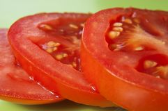 Tomato Slices on Green. Macro shot of three tomato slices on a green surface.  Skin and seeds visible Stock Photos