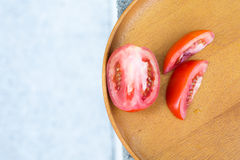 Tomato. Slices on a wooden plate Royalty Free Stock Images