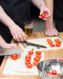 Tomato slicing. With knife on wooden table Stock Image