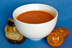 soup. Tomato soup in a white bowl  with bread and cut tomato on the side Royalty Free Stock Photography