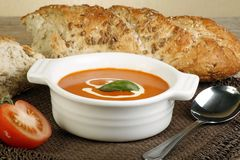 Tomato soup. And crusty bread on wooden table Stock Images