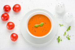 Tomato Soup. Aerial view of tomato soup on white wooden table with tomatoes basil salt and pepper shaker Stock Photo