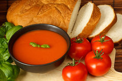 Tomato soup. Bowl of tomato soup with basil garnish, in kitchen setting surrounded by ingredients Stock Images