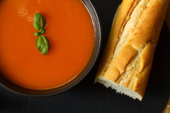 Tomato soup. Bowl of tomato soup and basil garnish with bread baguette Royalty Free Stock Images