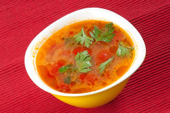 Tomato soup. In a yellow bowl on a red tablecloth Royalty Free Stock Image