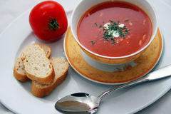 Tomato Soup. For Lunch on a dinner plate with spoon stock photography