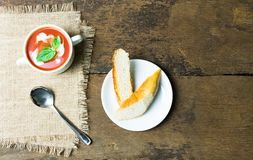 Tomato soup and baguette bread. Tomato soup in a white ceramic cup Decorated with basil and cream Put on sackcloth Side by side with a soup spoon and baguette stock images