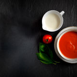 Tomato Soup with Basil with extended copy space. Overhead shot of fresh tomato soup with single cream, tomato and basil herbs. Selective lighting. Extended copy stock photos