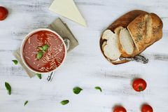 Tomato Soup with Basil Leaves and Bread. Hot tomato soup with basil leaves, parmesan cheese, fresh tomatoes and a loaf of herbed crusty bread. Image shot from Stock Images