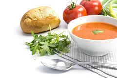 Tomato soup in a bowl with bread rolls and arugula on a white ba Royalty Free Stock Photography