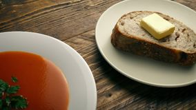 Tomato Soup And Bread On The Table. Tracking shot moving slowly past a bowl of soup next to a plate of bread and butter stock video