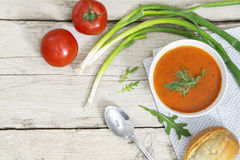 Tomato soup with bun, green onions and arugula garnish on bright Royalty Free Stock Photography