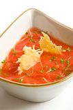 Tomato soup with cheese chips. White bowl of tomato soup with cheese chips stock photo