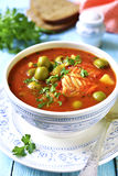 Tomato soup with cod,potato and olives. Tomato soup with cod,potato and olives in a vintage bowl royalty free stock photo