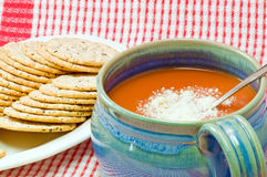 Tomato soup and crackers. A bowl of hot, delicious tomato soup in a blue soup mug or cup with cheese topping on a red plaid background Royalty Free Stock Images