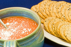 Tomato soup and crackers. A bowl of hot, delicious tomato soup in a blue soup mug or cup with cheese topping on a blue background Royalty Free Stock Images