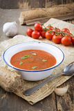Tomato soup. With cream, garlic, basil leaves and grinded black pepper, served with whole bread in a vintage metallic dish Stock Photo