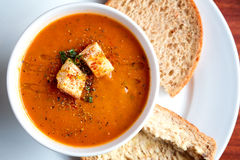 Tomato soup and croutons. A bowl of fresh tomato soup in white ceramic bowl, garnished with herbs, croutons, seasoning and a drizzle of olive oil, and served Royalty Free Stock Photos