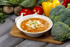 Tomato soup and fresh raw vegetables. In the background. Wooden rustic table, selective focus Stock Images