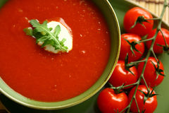 Tomato soup with garnish. Fresh tomato soup with sour cream and arugula garnish and tomatoes on the vine royalty free stock photography