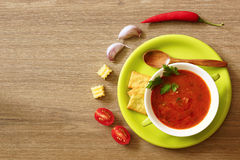 Tomato soup gazpacho  in a green cup on a wooden table. Top view. Royalty Free Stock Photos