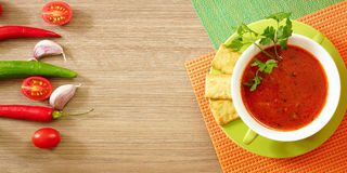 Tomato soup in a green cup on a wooden table. Top view. Free space for text Royalty Free Stock Images