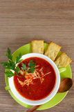 Tomato soup in a green cup on a wooden table. Top view. Stock Photo