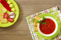 Tomato soup in a green cup on a wooden table. Top view. Royalty Free Stock Photo