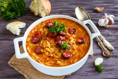 Tomato soup with orzo and smoked sausages in white casserole on wooden rustic table. Fresh bread and parsley, vintage spoon Royalty Free Stock Image