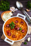 Tomato soup with orzo and smoked sausages in white casserole on wooden rustic table. Fresh bread and parsley, vintage spoon Royalty Free Stock Photo