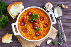 Tomato soup with orzo and smoked sausages in white casserole on wooden rustic table. Fresh bread and parsley, vintage spoon Royalty Free Stock Images