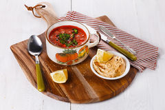 Tomato soup over white wooden background Royalty Free Stock Images