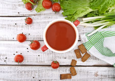 Tomato soup in red ceramic bowl on rustic wooden background. Hea Royalty Free Stock Image