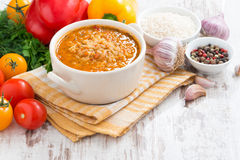 Tomato soup with rice and vegetables on white wooden background Royalty Free Stock Photo