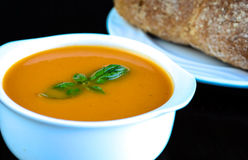 Tomato Soup with sides. Tomato and Basil soup with freshly baked bread roll Stock Photo