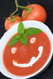 Tomato soup smiley. Tomato soup with basil leafs and smiley face as decoration Royalty Free Stock Images