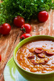 Tomato soup with smoked sausage, tomatoes and lentil. Soup: tomato soup with smoked sausage, tomatoes and lentil. Green bowl on wooden table. Small cherry Stock Images